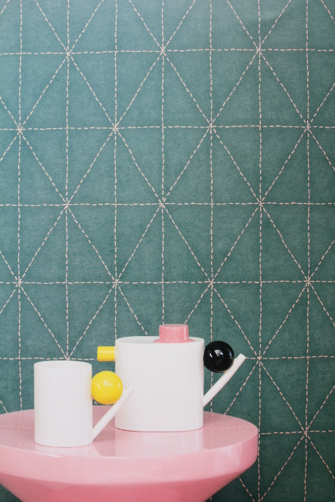 teal geometric patterned wallpaper with stitching